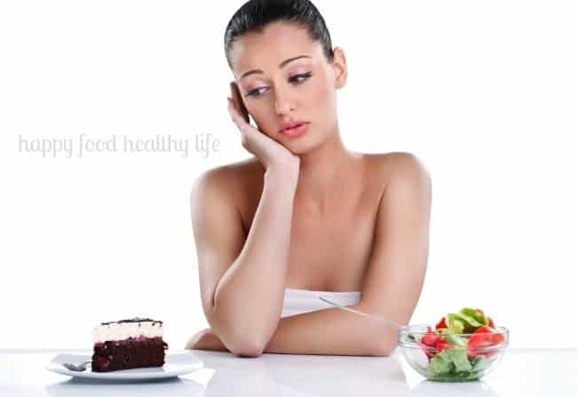 Young woman choosing between cake and healthy salad