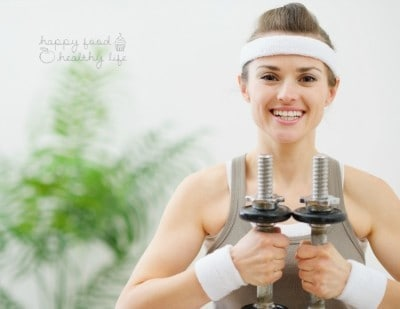 Portrait of happy fitness woman holding dumbbells