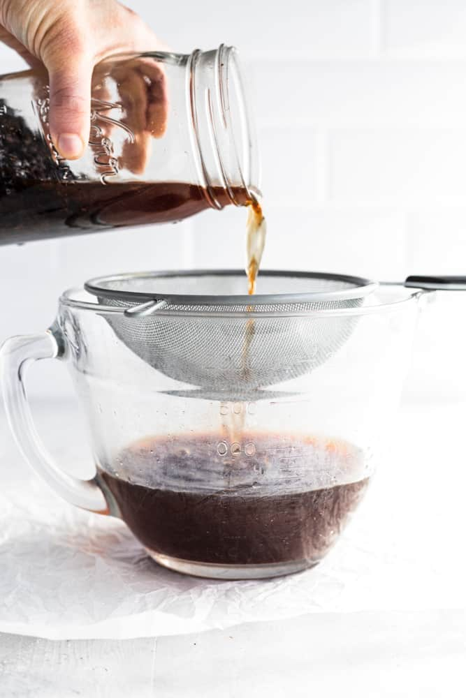 straining coffee grounds from cold brew coffee