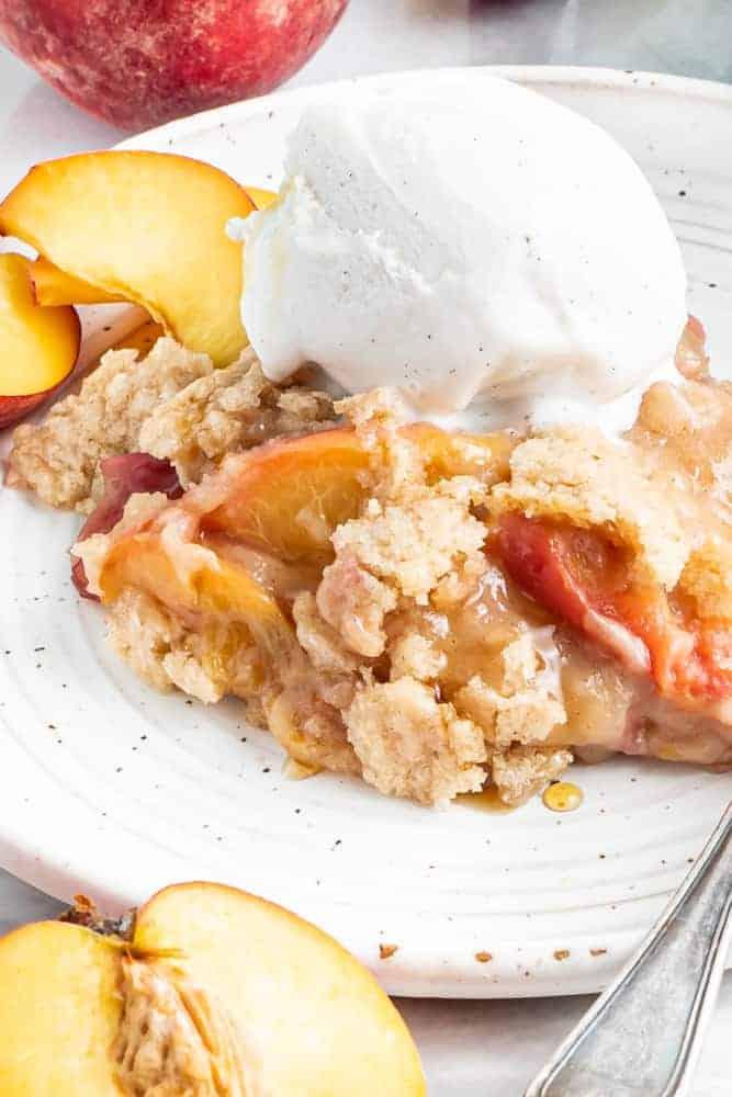 scoop of vegan peach cobbler with vanilla ice cream on top
