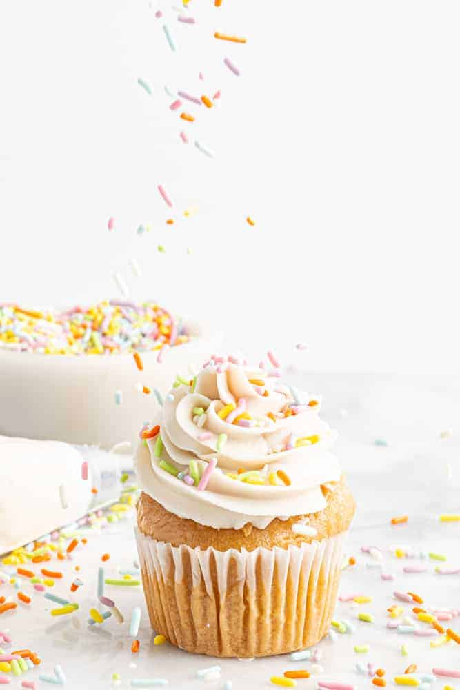 dairy-free frosting piped on cupcake with sprinkles falling on top