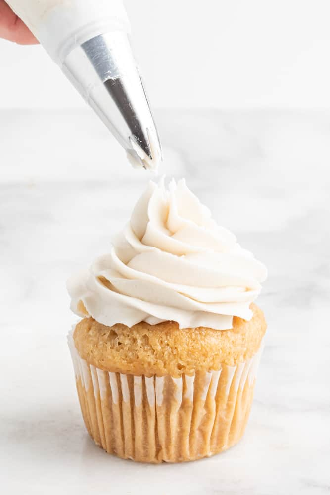piping vegan buttercream frosting on a cupcake